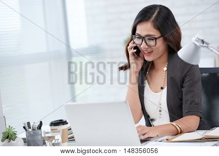 Smiling business lady talking on phone when working on laptop