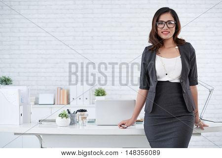 Cheerful Asian business lady standing at her workplace