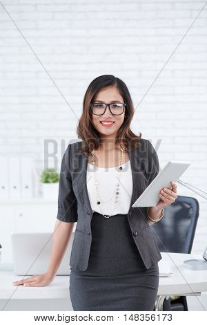 Portrait of smiling business lady with digital tablet in her hands
