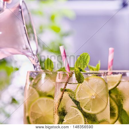 Alcohol cocktail. Top of glasses group with alcohol drink and striped cocktail straws. Drink number three hundred forty-seven cocktail mohito with mint leaf. Light background.