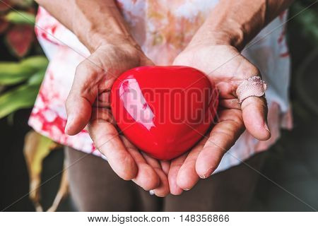 Elderly hands with wound carrying heart, vintage tone