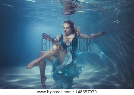 Woman in a dress dives underwater she dances on the bottom.