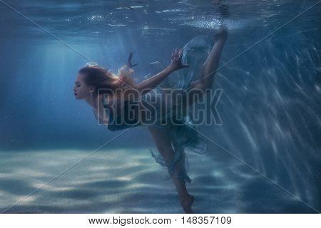 Woman in a dress is dancing underwater.