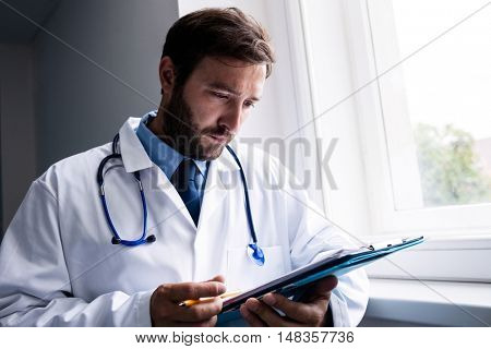 Doctor standing in hospital corridor looking at clipboard