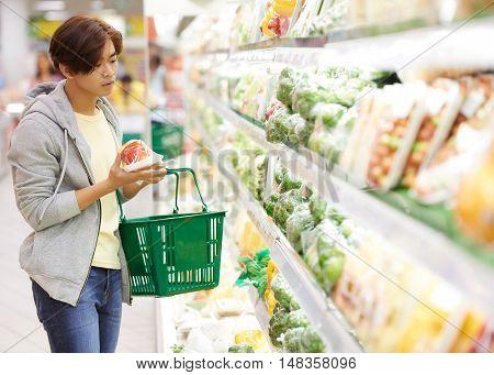 Vietnamese young man choosing vegetables in supermarket