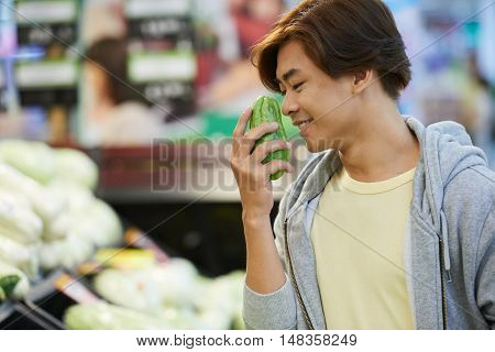 Vietnamese young man smiling when smelling guava
