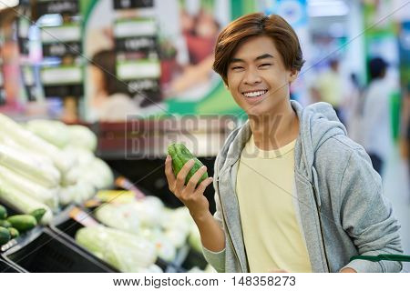 Cheerful Vietnamese guy shopping for fruits in supermarket