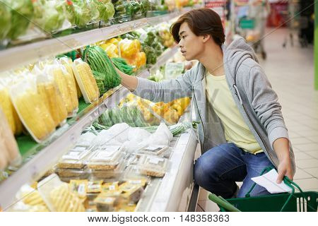 Vietnamese young man buying string beans in supermarket