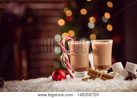 Composite image of hot chocolates against Christmas tree background