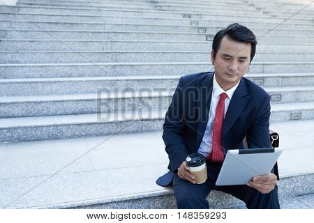 Asian businessman sitting on staircase and reading news in tablet computer
