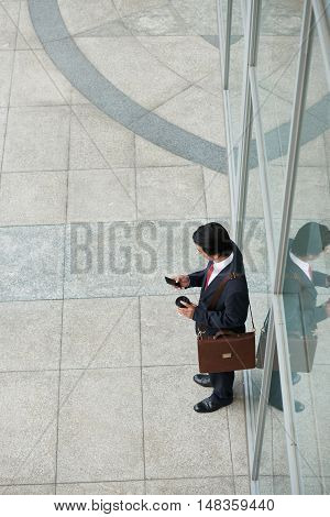 Businessman reading message in his phone when walking