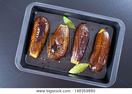 oven baked eggplants in baking dish with bay leaves and spices on black background view from above
