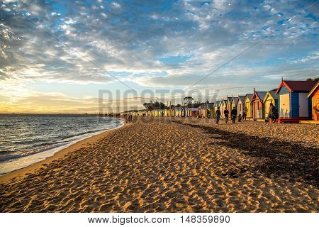 MELBOURNE AUSTRALIA - JULY 18 2016 : Tourists walk pass colorful bathing boxes at Brighton Beach near Melbourne Australia.