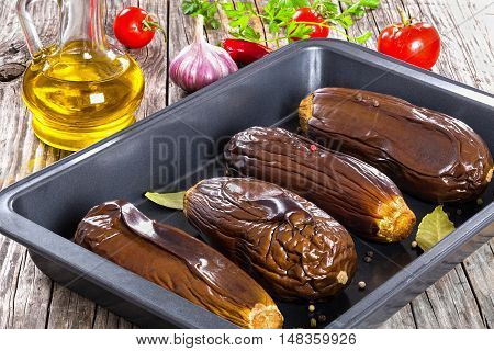 oven baked eggplants in baking dish with bay leaves and spices on woden boards view from above close-up