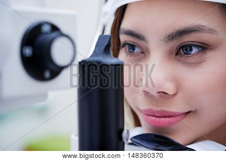 Face of young woman checking her eyesight in hospital