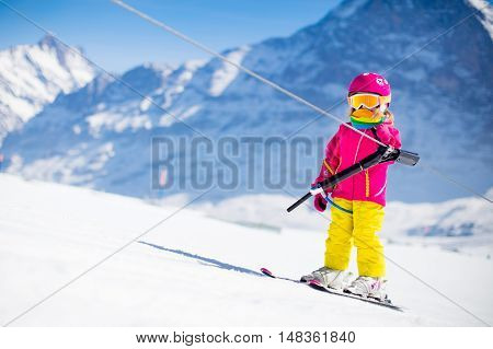 Child on a button ski lift going uphill in the mountains on a sunny snowy day. Kids in winter sport school in alpine resort. Family fun in the snow. Little skier learning and exercising on a slope.