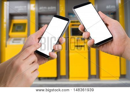 human hand hold and touch smartphone tablet cell phone with blank screen virtual internet banking on blurry cash machines background transfer money concept.