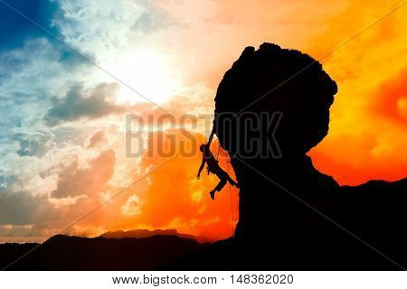 Lone Climber Almost At The Top Of The Mountain At Sunset With A Colorful Sky