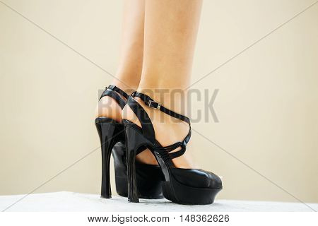 Black shoes female fancy high heel pumps strappy sandals on woman legs beautiful feet on white floor