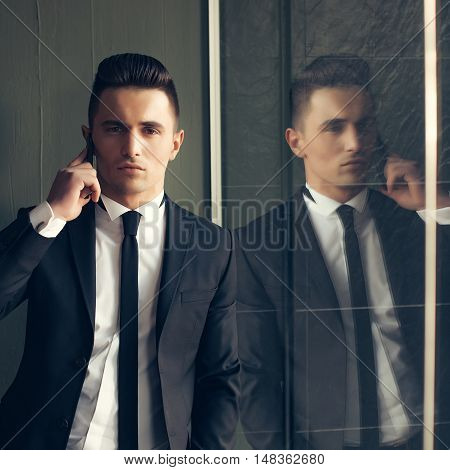 Man young handsome sensual elegant model in suit with skinny necktie open coat talks on mobile phone looks in camera hand in pocket reflects in mirror on grey background