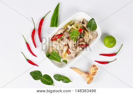 Chicken and galangal in coconut milk soup and herb on white background. Top view