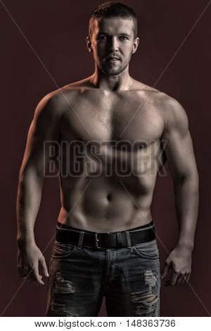 One sexual strong young man with muscular body in jeans looking forward standing posing in studio on red background vertical picture