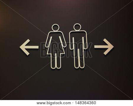 Sign of public restroom women and men on black background