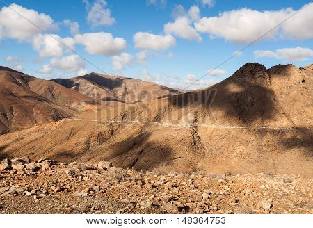Beautiful volcanic mountains and the road on a mountain slope. Road from la Pared to Betancuria . Fuerteventura. Canary Islands