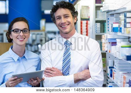 Portrait of pharmacists using digital tablet in pharmacy