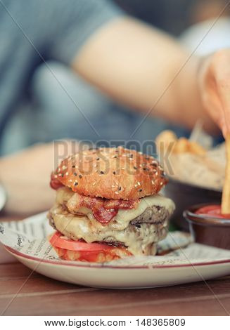 Double cheeseburger on table  in outdoor restaurant with shallow depth of field. Blurred young man in background.