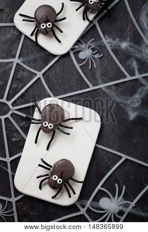 Dark grey spider macaroons with licorice