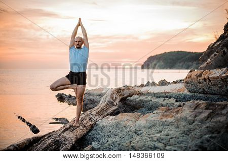Yoga posture on sunset by man near sea