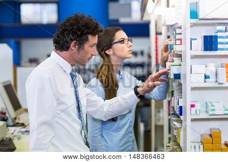 Pharmacists in lab coat checking medicines on shelf in pharmacy