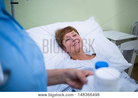 Nurse giving medication to patient in hospital ward