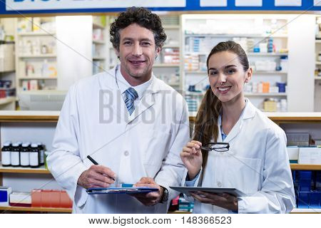 Portrait of smiling pharmacists with clipboard and digital tablet in pharmacy