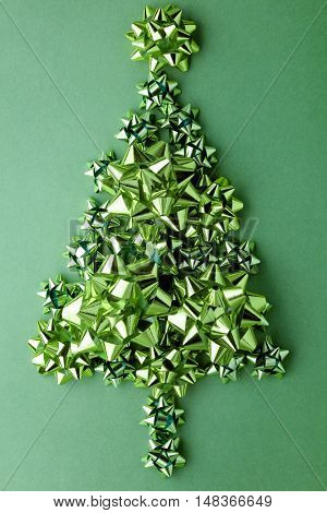 Christmas tree of glitterl bows on green background