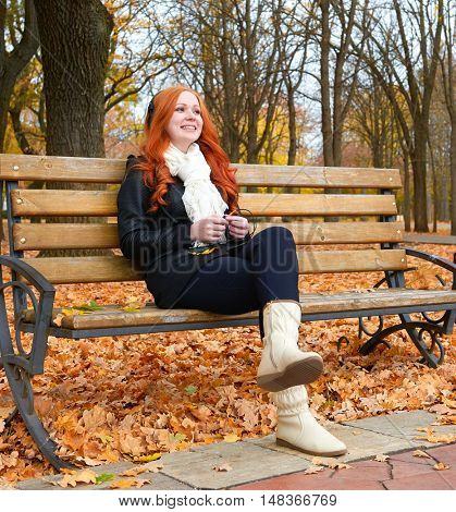 girl in fall season listen music on audio player with headphones, sit on bench in city park, yellow trees and fallen leaves