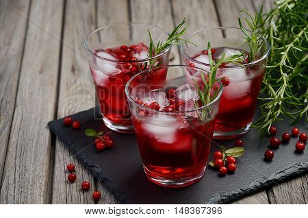 Refreshing drink with cranberries and rosemary on wooden background, selective focus, copy space