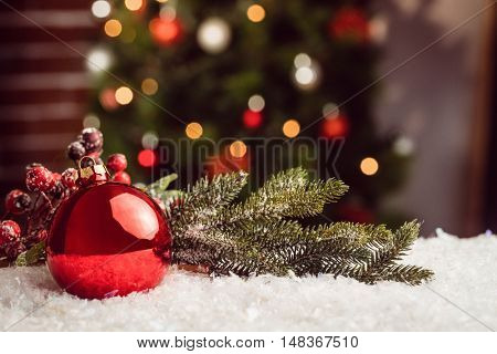 Composite image of Christmas bauble and holly against Christmas tree background