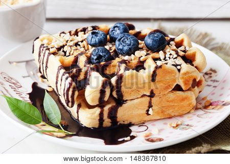 Belgian waffles with peanut chocolate sauce and blueberry bilberry whortleberry huckleberry hurtleberry blaeberry on a plate in still life straw