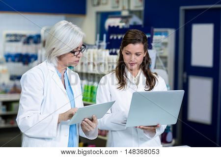 Pharmacists using digital tablet and laptop in pharmacy