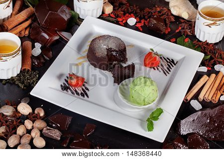 Brownie with ice cream pistachio strawberry mint in still life beautiful fresh ingredients