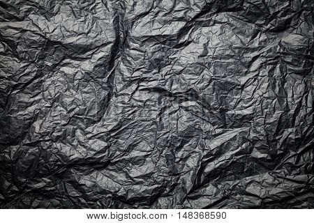 The dark texture of crumpled paper black background.