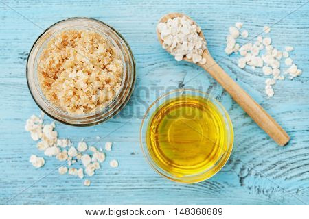 Body scrub of oatmeal sugar, honey and oil in glass jar on blue rustic table. Homemade cosmetic for peeling and spa care, top view.