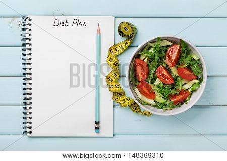 Diet plan menu or program, tape measure and diet food of fresh salad on blue background. Weight loss and detox concept, top view.