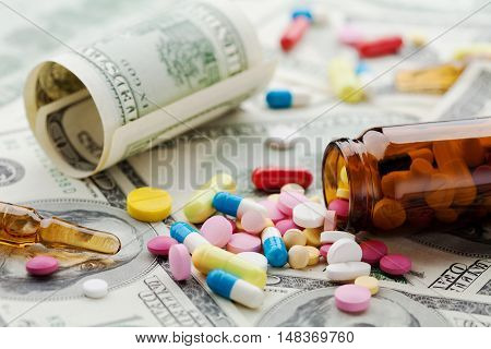 Pile of pharmaceutical drug and medicine pills on dollar money, cost of healthcare and medical insurance concept.