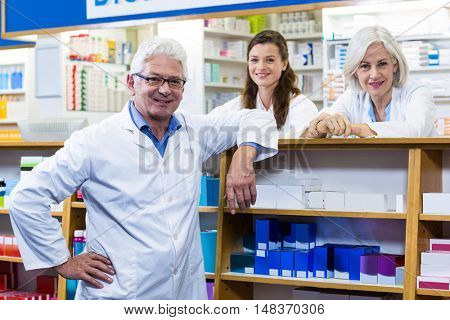Portrait of smiling pharmacists standing at counter in pharmacy