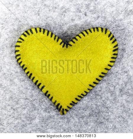 yellow felt heart on a gray background