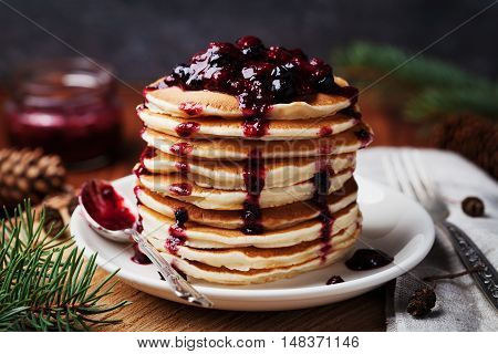 American pancakes or fritters served with strawberry and blueberry jam. Delicious dessert for breakfast in winter rustic style. Christmas concept.