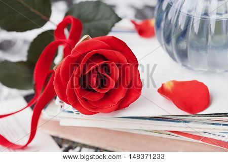 Red rose flower with a stack of postcard retro photos and vintage book.
